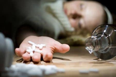 девушка без сознания держит в руках таблетки