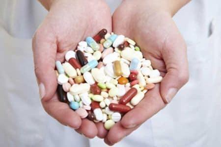 врач держит в ладонях таблетки