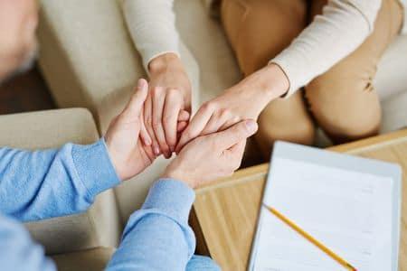 пациент и психолог держаться за руки