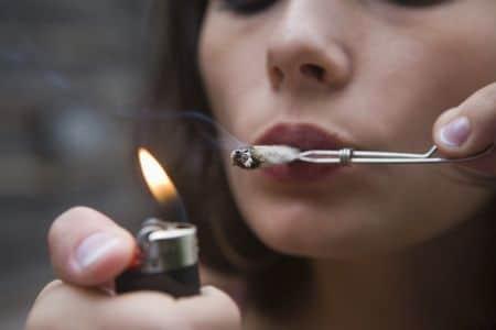 женщина подкуривает сигарету
