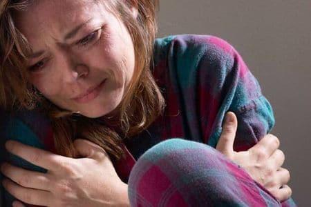 женщина плачет у стены