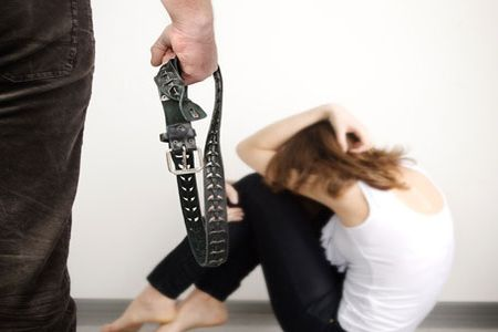 мужчина угрожает ремнем девушке
