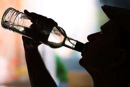 мужчина пьет водку из горла