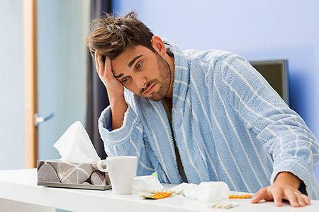 мужчина с простудой сидит за столом