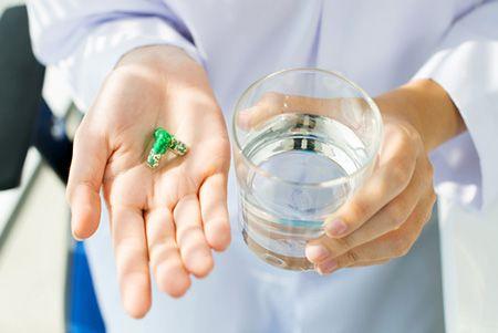 стакан воды и таблетка в руке