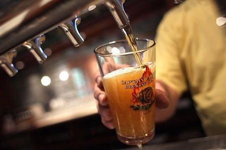 в стакан наливают пиво