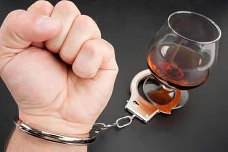 рука мужчины прикована наручниками к стакану с алкоголем
