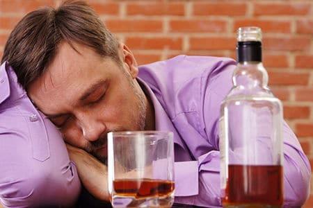 мужчина спит возле бутылки с алкоголем