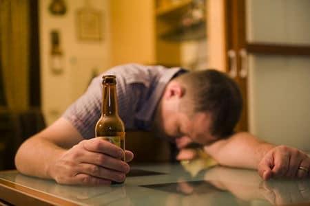 мужчина уснул за столом с бутылкой алкоголя