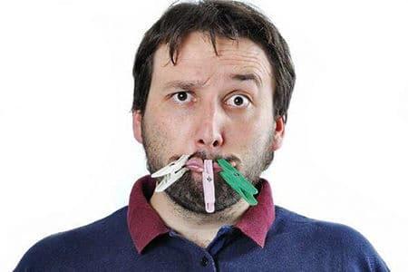 мужчина с прищепками на рту